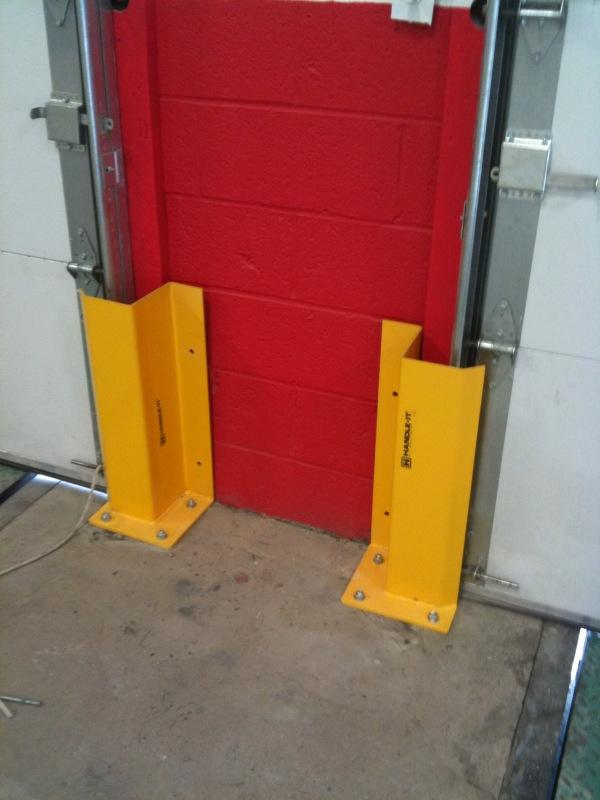 Handle It Track Guard Application between loading dock overhead doors.